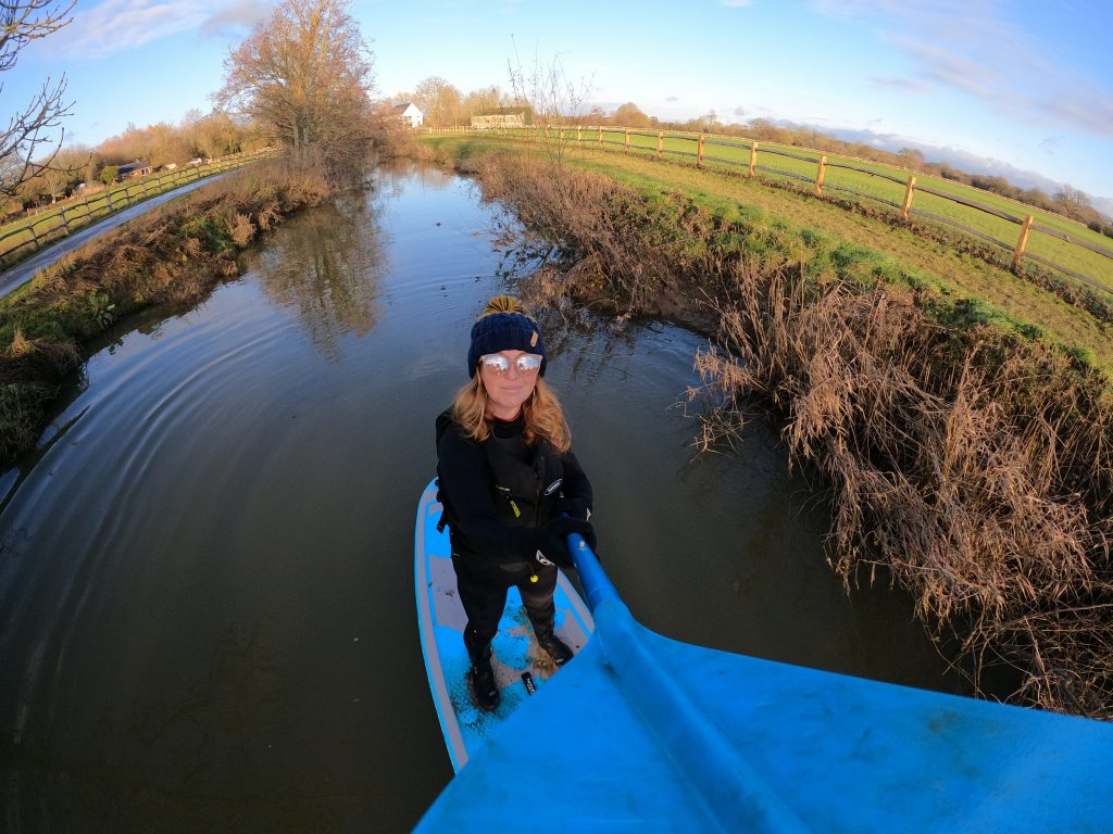 Stand up paddleboarder on a small river. Wearing bobble hat and sunglasses!
