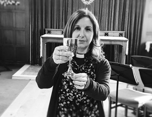 Female Priest holding up chalice at the communion table